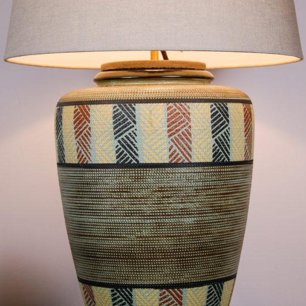 HOLA CHICA. Das Design der Lampe ist im mexican Style der 50er Jahre. Warme Farben und geometrische Muster kommen hier zusammen. Ein Traumteil! Die erdverbundenen Farben erinnern auch an das INKA-Volk mit Ihren Höhlenmalereien. Die Farbtöne bewegen sich zwischen Sand, Weinrot, hellblau, Schwarz, und einem erdigen Braun. Das geometrische Muster ist in den getöpferten Korpus eingeritzt.