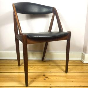 Kai Kristiansens M31 Teakholzstuhl aus den 1960er Jahren ist eine Design Liebling der Mid Century Modern Anhänger. Ein beliebter Esszimmerstuhl. Hier ein Einzelstück, das sich perfekt als Schreibtischstuhl, verwenden lässt. Die Lehne ist rundgeformt, sodaß sich er Rücken wunderbar in die Lehne legen kann. Der Bezug ist aus schwarzem Kunstleder. Original, wie es zu der Zeit verwendet wurde. Heute ist dieser Stuhl wieder ausserordentlich beliebt.