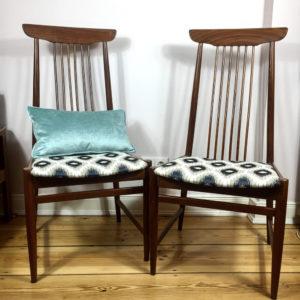Midcentury modern Esszimmerstühle mit hoher Lehne aus Teakholz. Die Stühle stammen aus Skandinavien. Bezogen wurden die Stühle mit einem gewebten Jacquard Stoff in einem weiss, beige marineblauem Bohemian Muster in abwechselnder Rhombenform. Die hohen Lehnen der Stühle haben am Rückenteil 6 schmale, hochverlaufende Streben, die in zwei breitere Streben eingefasst nach oben in einem schiffchenähnlichem Oberteil enden.