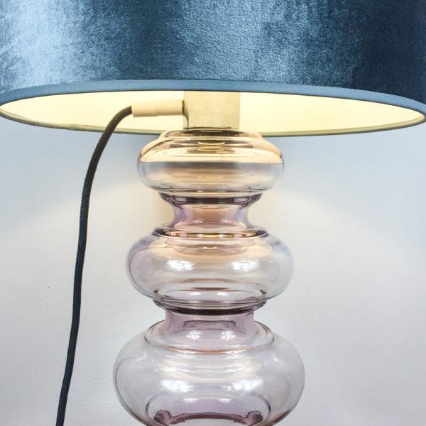 Eine sehr schöne Lampe mit einem Glaskorpus aus leicht rosé getöntem Glas. Trotz ihrer Größe vermittelt die Lampe Leichtigkeit. Der Schirm ist aus taupe-farbenem Samt. Der Korpus besteht aus 6 Glasringe, oder Ausbuchtungen, die sich von unten nach oben verjüngen, also schmaler werden.