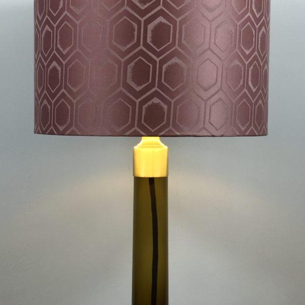 Tischlampe Glas Braun. Flacher, breiter Fuss mit langem Hals mit einer Messingmontur für die Fassung. Darauf ist der Lampenschirm befestigt. Dieser ist mit einem geometrischen Art Deco Design in Altrosa bespannt.