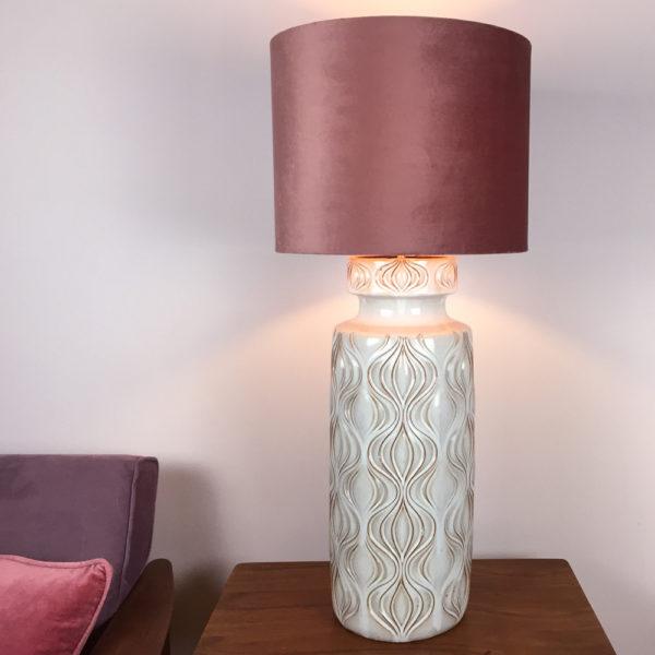 Der Lampenfuss ist ursprünglich eine Vase der Firma Scheurich. Das Modell Scheurich 285-53 hat ein angedeutetes Zwiebelmuster. Die Lasur ist Creme und sandfarben. Der Schirm ist aus altrosa farbenem Samt. Die Zuleitung ist aus grauem Textilkabel. Schalter und Stecker sind aus glänzendem, schwarzen Kunststoff im Retrolook.