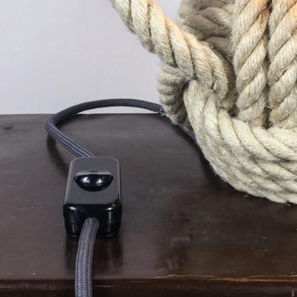 Die aus einem Hanftau hergestellte Affenfaust dient als Lampenfuss. Die Affenfaust hat einen Durchmesser von 20cm. Die Gesamthöhe beträgt ca. 30cm. An der Affenfaust befindet sich ein längeres Stück Tau, das herausragt und somit als Griff dient. So kann die Lampe an einen anderen Platz getragen werden. Der Lampenschirm ist aus einem maritimen, gestreiften blau und weissem Stoff gefertigt. Die Streifen sind 1cm breit, quer verlaufend und wechseln sich im Muster jeweils ab. Das Textilkabel ist ca. 2,5 m lang.