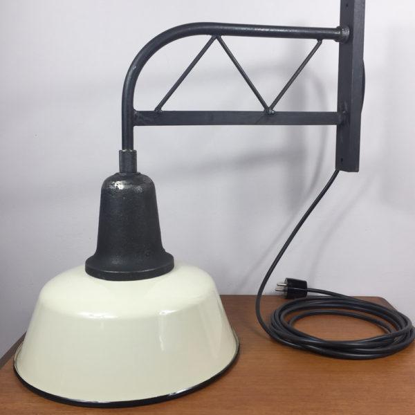 Die alte Industrielampe kann in der Küche über einem kleinen Frühstückstisch hängen, oder im Flur ein echter Hingucker sein. Zum Beispiel oberhalb eines Regales, oder auch als Leselampe an der Wand um im Bett lesen zu können. Das Gestell ist aus geschwärztem Stahl, wobei die Unebenheiten vom Gießen des Gestelles grau glänzend durchscheinen. Der Schirm ist mit Emaille versehen. Aussen cremefarben und innen kaltweiss. Der Schirm ist aussen mit einem schwarzen Rand versehen. Der Zustand ist wie neu. Die Lampe ist mit einer E27 Fassung ausgestattet. Das Kabel verläuft innerhalb des Wandgestänges.
