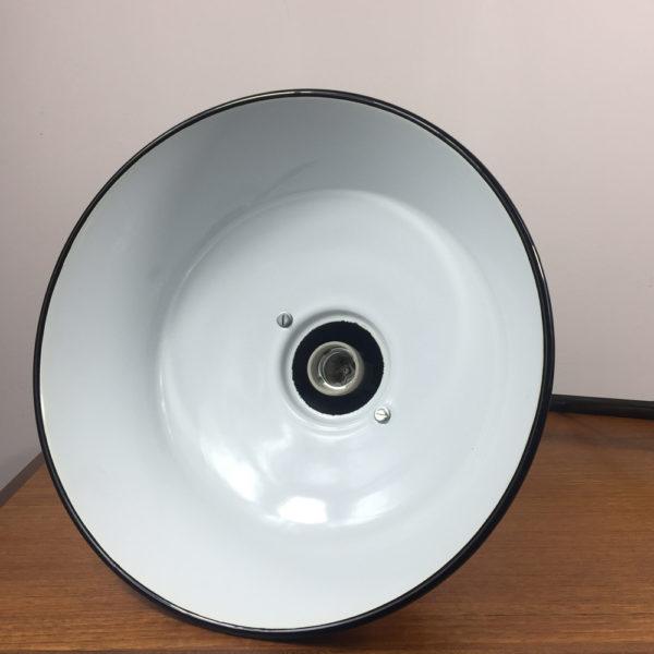Die alte Industrielampe kann in der Küche über einem kleinen Frühstückstisch hängen, oder im Flur ein echter Hingucker sein. Zum Beispiel oberhalb eines Regales, oder auch als Leselampe an der Wand um im Bett lesen zu können. Das Gestell ist aus geschwärztem Stahl, wobei die Unebenheiten vom Gießen des Gestelles grau glänzend durchscheinen. Der Schirm ist mit Emaille versehen. Aussen cremefarben und innen kaltweiss. Der Schirm ist aussen mit einem schwarzen Rand versehen. Der Zustand ist wie neu. DIe Lampe ist mit einer E27 Fassung ausgestattet.