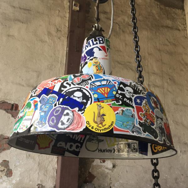 Die alte Industrielampe ist emailliert. Aussen schwarz und innen weiss. Als Aufhängung für die Deckenlampe ist am Schirm mittels eines alten Schekels eine massive, alte Kette aus der Industrie angebracht. Daran hoch windet sich das graue Textilkabel. Die Aufkleber aus den letzten dreißig Jahren spiegeln Freizeit, Beruf, Dienstleistungen, Speisen, Getränke, Kneipen, Discos und angesagte Sportartikelhersteller wieder. Die Lampe sieht als Küchenlampe, oder auch als Esstischlampe sensationell aus. Sie kann mit modernen, als auch mit antiken Einrichtungen kombiniert werden.