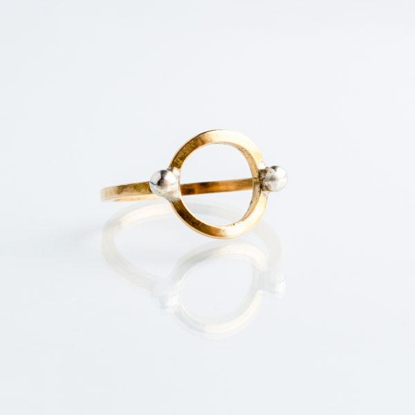 Ein Ring, gefertigt aus 1,5mm starkem Vierkant Messingdraht. Auf dem Ring sitzt ein Kreis, der ebenfalls aus Vierkantdraht gefertigt ist. Auf den Ring sind auf 9:00 und 3:00 Uhr zwei kleine Silberkugeln gelötet. Der Messingdraht leuchtet von der Farbigkeit her so wie 750er Gelbgold. Der Ring wird hier im room27 handgefertigt und mit einem Ringmaß speziell angefertigt für den Kunden.