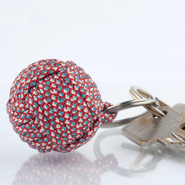 Seglerknoten Affenfaust. Ein Schlüsselanhänger aus blau, rot, weiss gemusterten Paracordseil. Salut France. Ein DIY Produkt. Der Schlüsselanhänger ist mit einem 3,2cm großen Edestahlfederring versehen. Die Farben sind erfrischend und sportlich.