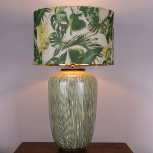 Die Lampe Botanical war ursprünglich eine Vase aus den 50er Jahren. Mit ihrem senkrecht verlaufenden Streifendesign in einem blassen Gelb und Grau, spiegelt die Vase die 50er Jahre wieder. Durch meine Idee, einen Deckel zu konstruieren, der die Gewindestange für den Lampenschirm als auch die Elektrik beinhaltet, kann die ehemalige Vase nun als Lampe erstrahlen. Der Lampenschirm ist mit seinem floralen Blattdesign sehr erfrischend. Für den kommenden Frühling ein Hingucker. Die goldenen Innenseite des Schirmes gibt ein schönes, warmes Licht ab.Die Lampe kann auch als Vase verwendet werden, da der Deckel nur in die Vase eingelassen ist. Wenn Sie eine kleine Wohnung haben und der Besuch bringt einen Blumenstrass mit, dann können Sie die Lampe zur Vase umfunktionieren.