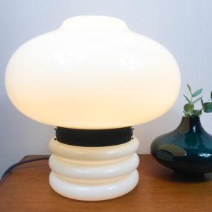 Für ein modernes zu Hause. Wer auf die Space Age Ära steht, sollte sich diese Lampe unbedingt für zu Hause kaufen. Die Tischlampe besteht komplett aus weissem, opakem Glas. Der obere Teil ist in der Form einer Blase gestaltet und wird durch einen schwarzen Metallring vom unteren Teil unterbrochen. Hier wird auch die Lampe geöffnet, wenn man das Leuchtmittel austauschen möchte. Der schwarze Metallring ist das Verbindungsstück zwischen dem Oberteil und Unterteil der Tischlampe. Der untere Teil der Tischlampe besteht ebenfalls aus weissem, opakem Glas und ist aus einer zylindrischen Form, die drei ringförmige Auswölbungen nach aussen hat. Die Gesamthöhe der Lampe beträgt 36cm. Die Kugel (Bubble) hat einen Durchmesser von 40cm. Der zylindrische Fuss mit den Auswölbungen hat einen Durchmesser von 20cm und eine Höhe von 16cm inkl. des schwarzen Metallringes. Dementsprechend ergibt sich eine Höhe von 20cm für die Blase, die den Lampenschirm darstellt.