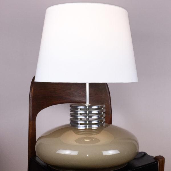 Die Lampe ist im Querschnitt betrachtet ein ovaler, hellbrauner Acrylkorpus, der mit einem Zwischenstück aus Aluminium besteht. Die Unterseite des Korpus ist flach. Dieses Zwischenstück hat mehrere Rippen und sieht aus wie ein Motorradzylinder. Das Design der Lampe sieht technisch aus. Der braune Korpus gibt jedoch mit seinem hellbraunen Korpus viel Wärme. Der Korpus ist nicht beleuchtet. Der Lampenschirm ist weiss. Vintage mit hohem Anspruch.