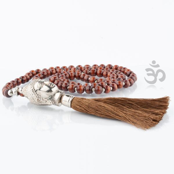 Die Buddhakette besteht aus kleinen, silber glänzenden Metallkugeln und doppelt so großen Holzkugeln in schwarz, die abwechselnd zu einer 90cm langen Kette aufgezogen sind. Mittig, unten befindet sich ein sehr schön ausgeformter Buddhakopf, der an der Unterseite seines Halses eine Quaste hat, die in der gleichen Farbe (Natur) der Holzperlen ist. Hiermit bist Du ganz im Yoga Feeling. Die Kette ist schön und gleichzeitig bist Du gut aufgehoben im Sinne von Buddha. Die schützende Hand von Buddha ist über Dir.