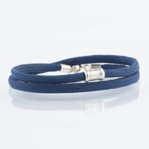 Ein handgefertigtes Armband aus Paracordseil, das zweimal um das Handgelenk gelegt wird. Der Karabinerverschluss mit Endkappen und Ösen und die auf der Vorderseite angebrachte Schmuckperle ist aus 925er Sterllingsilber. Die Schmuckperle ist ca. 1,2cm breit. Das Paracordseil ist in Marineblau gewebt und einen Durchmesser von 0,4cm.