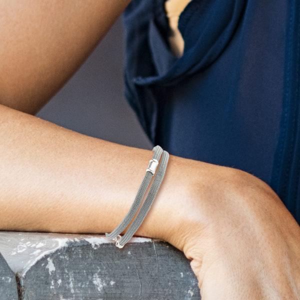 Ein handgefertigtes Armband aus Paracordseil, das zweimal um das Handgelenk gelegt wird. Der Karabinerverschluss mit Endkappen und Ösen und die auf der Vorderseite angebrachte Schmuckperle ist aus 925er Sterllingsilber. Die Schmuckperle ist ca. 1,2cm breit. Das Paracordseil ist in Grau gewebt und einen Durchmesser von 0,4cm.