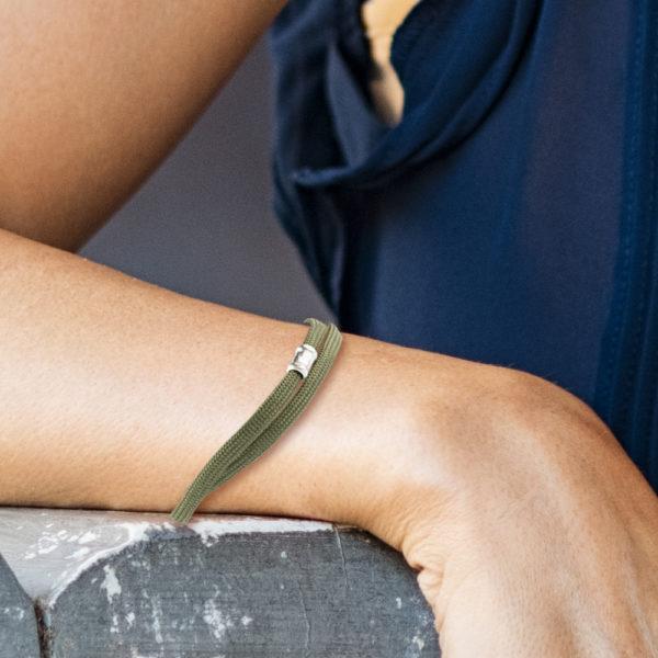 Ein handgefertigtes Armband aus Paracordseil, das zweimal um das Handgelenk gelegt wird. Der Karabinerverschluss mit Endkappen und Ösen und die auf der Vorderseite angebrachte Schmuckperle ist aus 925er Sterllingsilber. Die Schmuckperle ist ca. 1,2cm breit. Das Paracordseil ist in Oliv gewebt und hat einen Durchmesser von 0,4cm.