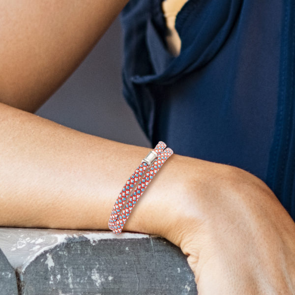 Ein handgefertigtes Armband aus Paracordseil, das zweimal um das Handgelenk gelegt wird. Der Karabinerverschluss mit Endkappen und Ösen und die auf der Vorderseite angebrachte Schmuckperle ist aus 925er Sterllingsilber. Die Schmuckperle ist ca. 1,2cm breit. Das Paracordseil ist in den Farben Blau, Weiss, und Rot gewebt und hat einen Durchmesser von 0,4cm.