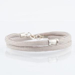 Ein handgefertigtes Armband aus Paracordseil, das zweimal um das Handgelenk gelegt wird. Der Karabinerverschluss mit Endkappen und Ösen und die auf der Vorderseite angebrachte Schmuckperle ist aus 925er Sterllingsilber. Die Schmuckperle ist ca. 1,2cm breit. Das Paracordseil ist in einem eleganten, warmen Sandton gewebt und hat einen Durchmesser von 0,4cm.