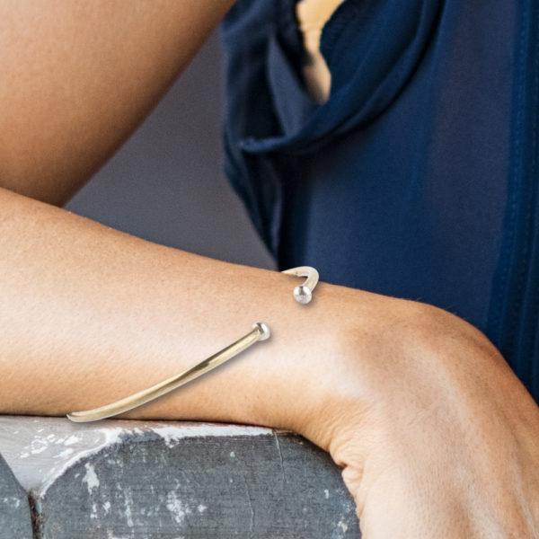 Eine Armspange, gefertigt aus 1,5mm starkem Runddraht aus Messing (Ms58). Auf der Armspange sind an der Öffnung, die zum Anlegen ans Handgelenk dient, jeweils an beiden Enden eine kleine Silberkugel angelötet worden. Der Messingdraht leuchtet von der Farbigkeit her so wie 750er Gelbgold. Die Armspange wird hier im room27 mit Deinem Hangelenkumfang speziell angefertigt. Hier findest Du Dein Handgelenkmaß auf der Tabelle. Der Durchmesser multipliziert mit 3,14 ergibt den Umfang. Also bei 6cm an der breitesten Stelle hast Du eine Handgelenksgröße von 20cm.