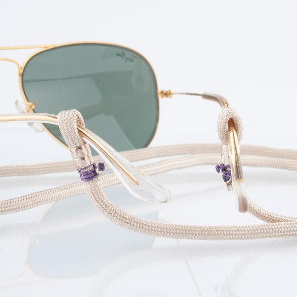 Brillenband Paracord Creme und Silber. Der Cremeton ist zart wie Champagner. Die Farbe kann zum Casual Look als auch zum klassischen Outfit getragen werden. Zu Creme passen im Kontrast zum Beispiel alle Jeanstöne, aber auch alle anderen Farben kannst Du zu diesem Tontragen. Ein klassisches Dunkelblau mit einem modernem Look, oder auch zum Anzug. Ganz egal. Auch knallige Farben passen zu diesem Brillenband. Das ist das tolle an diesem Brillenband. Das Brillenband ist sehr hochwertig verarbeitet und ist auf Langlebigkeit ausgerichtet. Die Perlen, die den Brillenbügel halten sind aus 925er Sterlingsilber. Das Brillenband hat jeweils an den Enden eine Schlaufe, durch die die Brillenbügel gesteckt werden. Die Schlaufen sind mit lila 1,0 mm Nylonband fixiert.