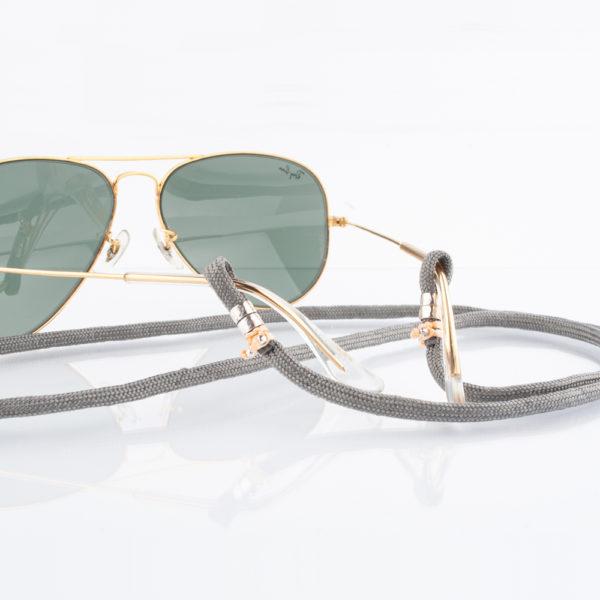 Brillenband Paracord grau und Silber. Der Grau ist dezent. Die Farbe kann zum Casual Look als auch zum klassischen Outfit getragen werden. Zu Grau passen im Kontrast passen sehr gut Knallfarben. Orange, pink, lila, türkis aber auch alle anderen Farben kannst Du zu diesem Ton tragen. Ein klassisches Grau mit einem modernem Look, oder auch zum Anzug. Ganz egal. Das ist das tolle an diesem Brillenband. Es ist ein tolles Accessoire, das zusätzlich noch Farbakzente setzt. Das Brillenband ist sehr hochwertig verarbeitet und ist auf Langlebigkeit ausgerichtet. Die Perlen, die den Brillenbügel halten sind aus 925er Sterlingsilber. Das Brillenband hat jeweils an den Enden eine Schlaufe, durch die die Brillenbügel gesteckt werden. Die Schlaufen sind mit lila 1,0 mm Nylonband fixiert. Kein lästiges suchen mehr. Du hast die Brille während Deiner Arbeit, oder im privaten Leben immer dabei. Nämlich um den Hals.