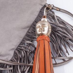 Der Schlüsselanhänger ist ein wahres Statement. Der Kopf ist 6 cm groß. Er ist ganz wunderbar ausgeformt. Mit seiner silbernen Metalloberfläche und der geschwärzten Patina hat der Kopf eine plastische Ausstrahlung. Der Hals des Buddhakopfes ist nach unten hin offen. Dort wird die gedrehte Lederquaste in cognac natur eingeschoben und das Metall wird mit der Quaste vernäht, sodaß sich beides fest verbindet. Um den Hals mit den Nähten zu kaschieren, wird aussen ein geflochtener Kragen umgewickelt und geklebt. Am oberen Teil des Kopfes ist auch ein Loch aus dem ein Lederriemen durchgeschoben wird und den Schlüsselring anbringen zu können.