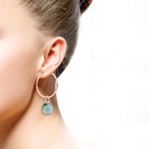 Die Creolen sind aus Edelstahl und mit Roségold vergoldet Die Ohrringe sind leicht, da sie hohl gearbeitet sind. Daran hängen Ösen mit Glastropfen aus klarem Muranoglas. Der Farbton verändert sich je nach Untergrund zwischen einem Aqua grün und Blau grau. Ein Farbton wie das Meer. Ein wunderschöner Ohrring, der durch seine Form dezent ist, jedoch durch den farbigen Tropfen auffällt. Der Tropfen scheint zu schweben aufgrund seiner Transparenz. Verschlossen werden die Ohrringe mit einem Bügel, der in eine kleine Klappvorrichtung gesteckt wird.
