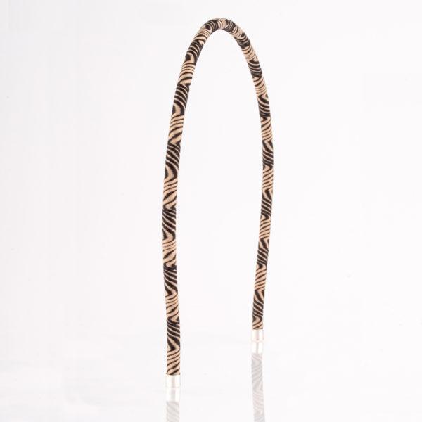 Der Haarreif ist aus Messingdraht gefertigt. Er ist mit einem schwarz camel farbenen Paracordseil in einem abwechselnden Wellendesign im Stil der 70er Jahre Tapetenmuster überzogen. Den Abschluss an den Enden bilden zwei 925er Sterling Silberkappen. Obwohl der Haarreif zart ist, hält er doch vorzüglich in den Haaren, da er am Kopf sehr gut anliegt. Ganz gleich, ob das Haar lockig, oder glatt ist. Der Haarreif ist 5 mm dick und ist somit ein zartes Modell.