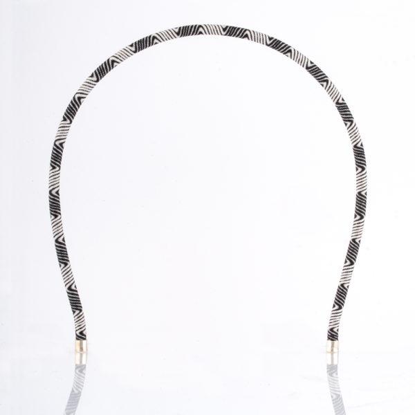 Der Haarreif ist aus Messingdraht gefertigt. Er ist mit einem schwarz weissen farbenen Paracordseil in einem abwechselnden Wellendesign im Stil der 70er Jahre Tapetenmuster überzogen. Den Abschluss an den Enden bilden zwei 925er Sterling Silberkappen. Obwohl der Haarreif zart ist, hält er doch vorzüglich in den Haaren, da er am Kopf sehr gut anliegt. Ganz gleich, ob das Haar lockig, oder glatt ist. Der Haarreif ist 5 mm dick und ist somit ein zartes Modell.