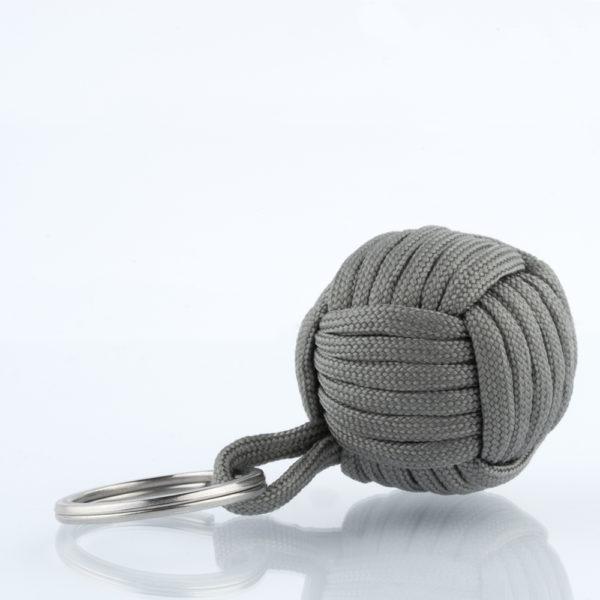 Seglerknoten Affenfaust. Ein Schlüsselanhänger aus einem grauen Paracordseil. Ein DIY Produkt. Der Schlüsselanhänger ist mit einem 3,2cm großen Edestahlfederring versehen. Die Affenfaust hat einen Durchmesser von 3,7cm.