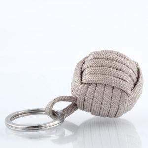Seglerknoten Affenfaust. Ein Schlüsselanhänger aus sandfarbenem Nudeton. Gefertigt aus einem Paracordseil. Ein DIY Produkt. Der Schlüsselanhänger ist mit einem 3,2cm großen Edestahlfederring versehen. Die Affenfaust selbst ist 3,7cm groß.