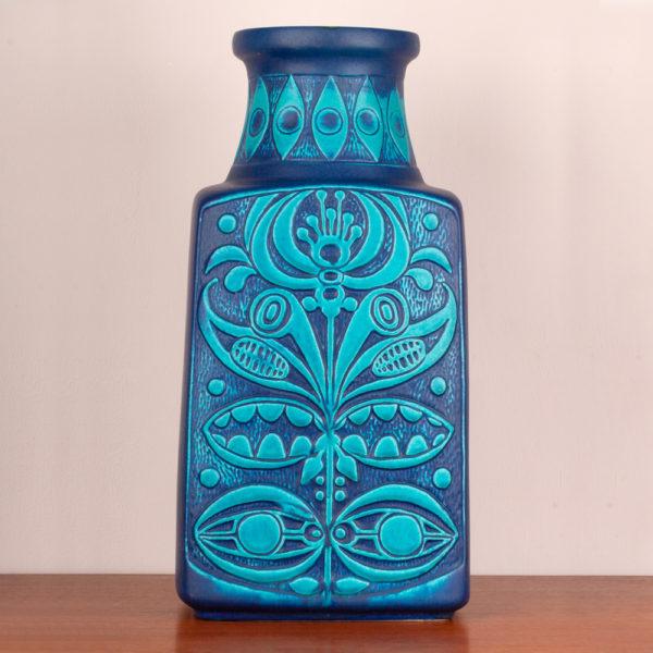 Die Bodenvase von der Firma Eduard Bay GmbH stammt aus den 1960er Jahren. Sie ist vintage. Also original aus der Zeit. Ihr Zustand ist gut. Die Farben blau und türkis sind kraftvoll. Das florale, typische Muster (es erinnert an die Wandmalereien und Bildhauerkunst der Inkas), das Bodo Mans als Designer verwendet hat, gibt es in verschiedenen Farbkombinationen. Diese Kombination ist toll und kann ganz wunderbar mit Teakmöbeln aus der Mid Century Modern Ära, aber auch mit derzeitigen Möbeln kombiniert werden. Gerade der Mix aus den vergangenen Jahrzehnten und den heutigen Modetrends in der Interiorszene ist spannend und eröffnet einem neue Perspektiven. Die Form, der Vase deutet eine Trapezform an. Unten ist die Vase breiter und verläuft verjüngend nach oben und endet im Vasenhals, der ganz oben eine kleine Krempe hat. Die Bodenvase, kann natürlich auf dem Boden glänzen, Du kannst sie aber auch als Tischvase verwenden. Gerade, bei der Größe der Vase, fällt sie optisch auf und ist ein Eye-Catcher und setzt damit ein Statement in Deinem zu Hause. Sei mutig und setze Akzente.