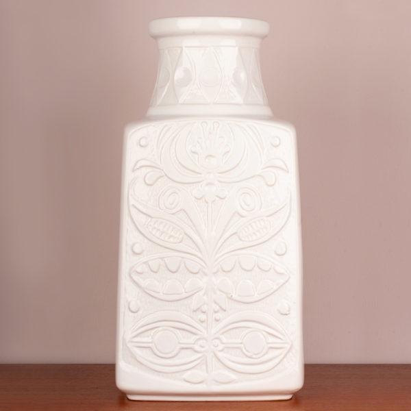 Die Bodenvase von der Firma Eduard Bay GmbH stammt aus den 1960er Jahren. Sie ist vintage. Also original aus der Zeit. Ihr Zustand ist gut. Die Farbe weiss ist edel. Das florale, typische Muster (es erinnert an die Wandmalereien und Bildhauerkunst der Inkas), das Bodo Mans als Designer verwendet hat, gibt es in verschiedenen Farbkombis. Diese Vase in weisser Optik ist sehr edel. Die Form, der Vase deutet eine Trapezform an. Unten ist die Vase breiter und verläuft verjüngend nach oben und endet im Vasenhals, der ganz oben eine kleine Krempe hat. Zur Info: Oben am Hals ist ein kleiner Sprung in der Lasur, der jedoch nur das Alter dieser schönen Vase widerspiegelt und fällt kaum auf, insbesondere gar nicht, wenn große, schöne Blumen in der Vase sind. Die Bodenvase, kann aber auch als Tischvase genommen werden. Gerade, bei der Größe der Vase, fällt sie optisch auf und ist ein Eye-Catcher und setzt damit ein Statement in Deinem zu Hause. Sei mutig und setze Akzente.