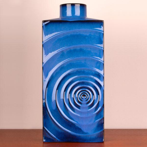 """Das Design dieser schönen Vase stammt von dem Designer Cari Zalloni der in den 1960er Jahren mit seiner Arbeit als Designer begann. Er arbeitete für das Keramikwerk Steuler bei Coblenz. Die Vase ist vintage. Also original aus der Zeit. Ihr Zustand hervorragend. Die Farbe blau ist sehr edel. Das Design """"Zyklon"""" ist ein stilisierter Wirbelsturm, der sich in Wellen von der Mitte aus nach aussen bewegt und somit eine interessante Struktur auf der Vase bildet. Licht und Schatten wechseln sich ab. Die blaue Lasur bewegt sich zwischen hellerem und dunklerem Blau. Das leuchtende Königsblau strahlt jedoch auf der gesamten Vase. Die Vase hat eine rechteckige Form, wobei sie oben in einem engen Hals endet. Die Vase kannst Du als Tischvase und auch als Bodenvase verwenden. Durch ihre kraftvolle Ausstrahlung kann sie Beides sein. Ein echter Eye-Catcher. Du setzt damit ein Statement in Deinem zu Hause. Sei mutig und setze Akzente."""