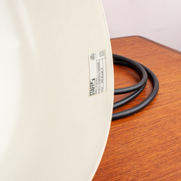 Die Hängelampe der Firma STAFF stammt aus den 1970er Jahren. Schlicht und sehr modern ist das Design. Aus der Ära USM Haller kommt diese Lampe. Der Metallkorpus ist pulverbeschichtet. Mit einem Cremeton. Die obige Abdeckung ist schwarz. Das Kabel ist schwarz und aus Kunststoff.Der Lampenschirm innen ist weiss. Auf der Innenseite zur Mitte hin, in der sich das Leuchtmittel befindet, gibt es einige kleine, oberflächliche Kratzer. Wenn die Lampe hängt sieht man diese minimalen Beschädigungen jedoch nicht.Diese Lampe ist mit antiken Möbeln, genauso wie mit modernem Interior kombinierbar.