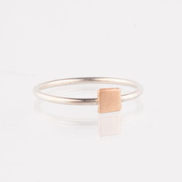 Ein Ring, gefertigt aus 1,5mm starkem Silberdraht. Auf dem Ring sitzt ein Quadrat aus Bronze. Das Quadrat ist handgesägt. Bronze leuchtet von der Farbigkeit her so wie Roségold. Der Ring wird hier im room27 handgefertigt. Mit Hilfe eines Ringmaßes wird speziell für die Kundin, oder den Kunden der Ring angefertigt. Hier findest Du Dein Ringmaß, beziehungsweise Deinen Ringumfang. Als Hilfe kannst Du Dir einfach einen Deiner bisherigen Ringe an ein Lineal halten und den Durchmesser ablesen.
