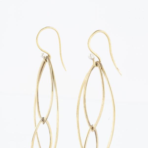 Ohrhänger Mobile aus Messing und Silber. Ohrhänger aus S-Haken. Ein Mobile in Form von drei verschieden großen Rhomben aus Messingdraht und kleinen Silberkugeln als Stopper für die Aufhängung der Rhomben. Runddraht, der von Hand flach gehämmert wurde und somit eine flache Form erhält. Durch die Hammerschläge sind in dem Metall kleine Unebenheiten, die die Ohrhänger individueller und lebendiger aussehen lassen. Handgefertigt eben und nicht von der Stange. Die ineinander gehängten Rhomben haben drei Größen. Da die Rhomben von Hand gefertigt sind, unterscheiden sie sich minimal in den Größen, leben dadurch aber viel mehr als industriell gefertigte Ohrringe.