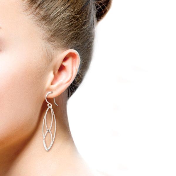 Ohrhänger Mobile aus 925er Silber. Ohrhänger aus S-Haken. Ein Mobile in Form von drei verschieden großen Rhomben aus 925er Silberdraht und kleinen Silberkugeln als Stopper für die Aufhängung der Rhomben. Runddraht, der von Hand flach gehämmert wurde und somit eine flache und zierliche Form erhält. Durch die Hammerschläge sind in dem Metall kleine Unebenheiten, die die Ohrhänger individueller und lebendiger aussehen lassen. Handgefertigt eben und nicht von der Stange. Die ineinander gehängten Rhomben haben drei Größen. Da die Rhomben von Hand gefertigt sind, unterscheiden sie sich minimal in den Größen, leben dadurch aber viel mehr als industriell, gleichförmige Stanzformen.