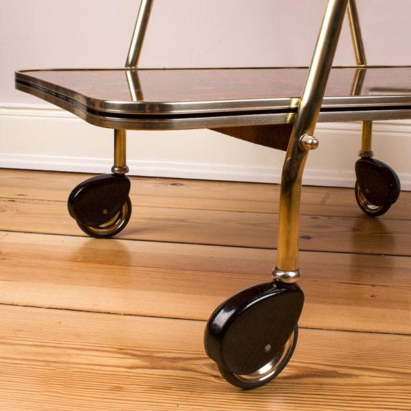 Der Servierwagen ist aus den 1950er Jahren. Das Gestell ist aus poliertem Messing. Die Platten sind mit einem Design aus den Fünfziger Jahren versehen und haben eine hochglänzendes Acrylschicht als Abschluss. Der Stil aus der Mid Century Ära ist der derzeitige Trend überhaupt. Diese Möbel lassen sich ganz wunderbar mit Möbeln von heute kombinieren. Die Räder sind mit einem Kunststoff bis zu Hälfte verdeckt. Wie ein Oldtimer aus Amerika, der im Stromlinien Design gestaltet ist.