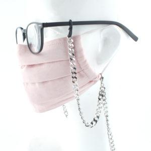 Die Masken Brillen Kette ist stylisch und zugleich eine effektive Hilfe im Alltag. Hier in Edelstahl, silber. Die Panzerkette ist ein Klassiker und findet sich in vielen Accessoires wieder. Zum Beispiel in den Tragriemen von den angesagten Handtaschen. Damit Du nicht ständig Deine Maske aus der Tasche holen musst, oder in der Hand hältst, hängst Du die Maske einfach um den Hals. An die Kette kannst Du die Maske, als auch Deine Brille befestigen. Die zwei Karabinerverschlüsse klemmst Du einfach an die Maske. Gleichzeitig kannst Du auch als Brillenträger die Brille am selben Band mit der Maske zusammen tragen. Für die Brille sind die Ösen aus Naturkautschuck vorgesehen, durch die Du die Brillenbügel durchsteckst. Jederzeit kannst Du somit die Brille absetzen, oder aufsetzen, ohne sie wegzulegen. Du solltest immer erst die Maske und dann die Brille aufsetzen.
