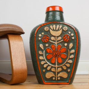Die Bodenvase von der Firma Eduard Bay GmbH stammt aus den 1960er Jahren. Sie ist vintage. Also original aus der Zeit. Ihr Zustand ist sehr gut. Die Farben sind bunt zusammengesetzt. Olivgrün, rotorange, crémegelb und schwarz. Die florale ornamentartige Blumenkomposition erinnern an die Inka Zeit. Der Look ist archaisch. Wenn man so will, ist die Lasur der einzelnen Farben bewusst nicht flächendeckend ausgefüllt worden, sodaß die Farben auf der Oberfläche grob aneinander grenzen. Die Vase kannst Du als Bodenvase, aber auch als Tischvase verwenden. Gerade, bei der Größe der Vase, fällt sie optisch auf und ist ein Eye-Catcher und setzt damit ein Statement in Deinem zu Hause. Sei mutig und setze Akzente. Die Vase hat eine bauchige Flaschenform. Von unten schmal, basierend auf einer rechteckigen Grundform mit bauchigen Seiten, wird die Vase nach oben breiter und läuft wieder zusammen zu einem krempenartigen Hals, der in rotorange glasiert ist. Die Vase hat einen Kunsstoffeinsatz. Dieser wird bis heute für diese großen Vasen angeboten, damit man nicht so viel Wasser in die Vase füllen muss.