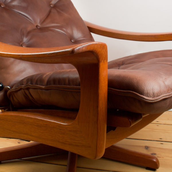 Dieser sehr gemütliche Sessel ist perfekt für den kurzen, tiefen Schlaf, oder auch um die Nacht darin zu verbringen. Die Rückenlehne lässt sich von der normalen Sitzposition zur Liegeposition mittels eines Metallgriffes an der Seite verstellen. Während Du in dem Sessel sitzt, kannst Du durch Gewichtsverlagerung die gewünschte Position einnehmen und mit dem Metallgriff feststellen. Das Leder des Sessels hat einen fuchsfarbenen Ton im Vintage Look und passt ganz wunderbar zu dem Teakholz aus dem der Sessel gefertigt ist. Der dazu gehörige Hocker dient als Ablage für die Füsse, kann aber auch mittels eines großen Tabletts als Beistelltisch neben dem Sessel genutzt werden. Das Leder des Hockers ist dunkelbraun. Ursprünglich gehörte der Hocker wohl mal zu einem dunkelbraunen Modell. Die verschiedenen Brauntöne passen aber wunderbar zusammen.