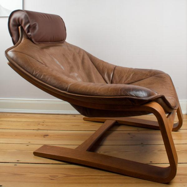 Aus diesem Sessel willst Du nicht mehr raus. Er ist wie ein Sitzsack, oder Fatboy. Eben wie eine gemütliche Höhle. Die Sitzposition ist sehr komfortabel und mittels der aufsteckbaren/abnehmbaren Kopfstütze kannst Du den Nacken komplett entspannen. Das Leder des Sessels hat einen fuchsfarbenen Ton im Vintage Look und passt ganz wunderbar zu dem Teakholz aus dem der Sessel gefertigt ist. Der dazu gehörige Hocker ist im selben geschwungenen Stil wie der Sessel konstruiert und sieht optisch wie eine Verlängerung aus. Du kannst den Hocker aber auch separat als Sitzgelegenheit, oder auch als Beistelltisch mit einem großen Tablett verwenden. Das Leder des Hockers hat denselben fuchsfarbenen Ton wie der Sessel. Der Sessel ist Vintage, somit hat er im Armlehnenbereich mehr optische Abnutzungen als auf der übrigen Fläche. Es sind keine durchgescheuerten Stellen am Leder zu sehen. Er ist eben Vintage. Das Sesselgestell, als auch der Hocker sind aus Schicht Teakholz geformt, also in Form gebogen. Beide Gestelle sind federnd. Die Kopfstütze wurde bereits mit neuem Leder bezogen und sieht wie neu aus.