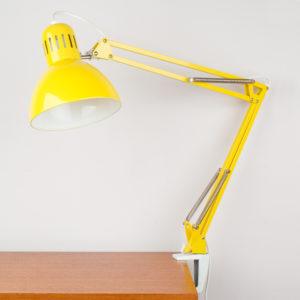 Die sogenannte Architektenlampe, ist eine Schreibtisch-, oder auch Arbeitslampe. Der Gelenkarm mit den vier Federn lässt sich je nach Bedarf in der Höhe und in der Tiefe durch ziehen und schieben verstellen und bleibt in der gewählten Position stehen. Der Metallschirm ist in der Horizontalen und Vertikalen durch ziehen, oder schieben ebenfalls verstellbar und bleibt auch in der gewählten Position stehen. Eine so praktische Lampe! Die sonnengelbe Pulverbeschichtung des Gestelles als auch des Schirmes ist in einem sehr guten Zustand. Bei der Farbe kommt Freude auf und die Lampe ist in ihrem Gelb ein wahres Revival. Der Schirm ist oben schmal und verbreitert sich zu einer Trichterform, die sich nach unten hin öffnet, sodaß ein breiter Lichtkegel entsteht. Oben in der Lampe sind Lüftungsschlitze. Ich empfehle ein LED-Leuchtmittel mit E27 Schraubgewinde. Der Vorteil dieser Leuchtmittel ist, daß sie nicht heiss werden. Die Lampe ist durch einen Sockel, der am Schreibtisch anschraubbar ist, befestigt. Das Gestänge wird in den Sockel gesteckt und ist so auch noch auf der Horizontalen Ebene drehbar.