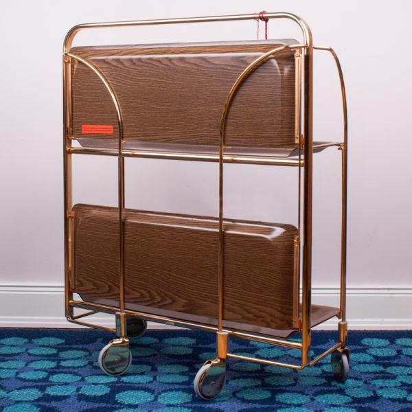 Ein praktisches und stylisches Einrichtungsteil ist dieser Servierwagen. Das Revival der 60er und 70er Jahre ist gerade angesagt. Der Servierwagen ist aus Messing und schimmert wunderschön in goldfarben. Er ist klappbar. So wie die typischen Servierwagen aus der Zeit, ist es möglich, entweder nur eine Seite mit den zwei Ablageflächen auszuklappen, oder beide Seiten auszuklappen und zu benutzen. Wenn nur eine Seite ausgeklappt ist, kann der Servierwagen in einer kleinen Wohnung wunderbar an der Wand stehen. Platzsparend kann der Servierwagen weggestellt werden, wenn beide Seiten mit den Ablageflächen hochgeklappt sind. Auf den vier Rollen aus hellgrauem Gummi und den Messingabdeckungen an den Rädern steht der Servierwagen sicher und kann zum Beispiel hinter einer Tür stehen. Die Ablageflächen sind aus Kunststoff mit einem warmen Holzfurnier versehen. Die Kombi Messing, goldfarben mit Holz vermittelt ein stylische Gemütlichkeit. Setze Highlights mit solchen Specials und gestalte aus dem Servierwagen Deine Bar, oder einen fahrbaren Tisch für das morgendliche, kleine Frühstück.