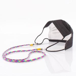 Das Maskenband ist der kleine Helfer im Alltag. Hier in der Farbkombi in Blau Pink Lila Gelb. Bunt ist für den Sommer immer perfekt. Sie passt sehr gut zu einer weissen Bluse, oder einem weissen Hemd. Damit Du nicht ständig Deine Maske aus der Tasche holen musst, oder in der Hand hältst, hängst Du die Maske mit dem Band einfach um den Hals und steckst sie Dir in die Tasche Deines Oberhemdes, oder in die Revertasche Deiner Jacke, wenn Du sie nicht benötigst. Sie kann aber auch einfach runterhängen. Ob Du bei der Arbeit bist, oder in ein Geschäft, oder ins Restaurant gehst, kannst Du sie schnell aufsetzen. Die zwei Karabinerverschlüsse klemmst Du einfach an das Gummiband, das bei Gebrauch um die Ohren gelegt wird. Durch das Eigengewicht hängen die Karabiner an der tiefsten Stelle des Gummibandes, sodaß sie auch nicht an den Ohren drücken können. Die Karabiner sind mit feinen Nylonbänder befestigt. Die Farben dieser Bänder kannst Du Dir über die Tabelle aussuchen. Die Maskenbänder werden dann daraufhin gefertigt. Stelle Dir Deine Farbkombi zusammen.