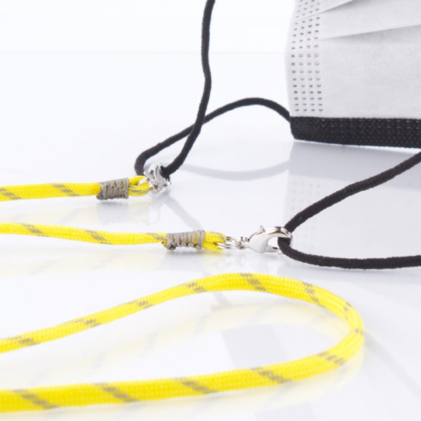 Das Maskenband ist der kleine Helfer im Alltag. Hier in der Farbkombi in Neon Gelb Grau. Neon ist für den Sommer immer perfekt. Sie passt sehr gut zu einer weissen Bluse, oder einem weissen Hemd. Damit Du nicht ständig Deine Maske aus der Tasche holen musst, oder in der Hand hältst, hängst Du die Maske mit dem Band einfach um den Hals und steckst sie Dir in die Tasche Deines Oberhemdes, oder in die Revertasche Deiner Jacke, wenn Du sie nicht benötigst. Sie kann aber auch einfach runterhängen. Ob Du bei der Arbeit bist, oder in ein Geschäft, oder ins Restaurant gehst, kannst Du sie schnell aufsetzen. Die zwei Karabinerverschlüsse klemmst Du einfach an das Gummiband, das bei Gebrauch um die Ohren gelegt wird. Durch das Eigengewicht hängen die Karabiner an der tiefsten Stelle des Gummibandes, sodaß sie auch nicht an den Ohren drücken können. Die Karabiner sind mit feinen Nylonbänder befestigt. Stelle Dir Deine Farbkombi zusammen.
