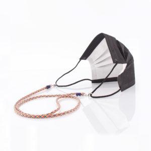 Das Maskenband ist der kleine Helfer im Alltag. Hier im 80er Jahre Surfer Look. Surfern heisst Sommer. Es passt sehr gut zu einer weissen Bluse, oder einem weissen Hemd. Damit Du nicht ständig Deine Maske aus der Tasche holen musst, oder in der Hand hältst, hängst Du die Maske mit dem Band einfach um den Hals und steckst sie Dir in die Tasche Deines Oberhemdes, oder in die Revertasche Deiner Jacke, wenn Du sie nicht benötigst. Sie kann aber auch einfach runterhängen. Ob Du bei der Arbeit bist, oder in ein Geschäft, oder ins Restaurant gehst, kannst Du sie schnell aufsetzen. Die zwei Karabinerverschlüsse klemmst Du einfach an das Gummiband, das bei Gebrauch um die Ohren gelegt wird. Durch das Eigengewicht hängen die Karabiner an der tiefsten Stelle des Gummibandes, sodaß sie auch nicht an den Ohren drücken können. Die Karabiner sind mit feinen Nylonbänder befestigt. Die Farben dieser Bänder kannst Du Dir über die Tabelle aussuchen. Die Maskenbänder werden dann darauf hin gefertigt. Stelle Dir Deine Farbkombi zusammen.