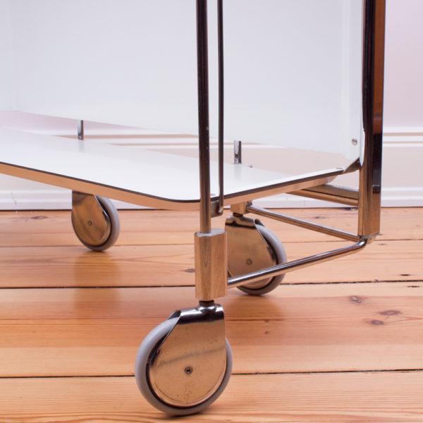 Ein praktisches und stylisches Einrichtungsteil ist dieser Servierwagen. Das Revival der 60er und 70er Jahre ist gerade angesagt. Der Servierwagen aus verchromtem Metall und schimmert wunderschön in einem poliertem Silberton. Er ist klappbar. So wie die typischen Servierwagen aus der Zeit, ist es möglich, entweder nur eine Seite mit den zwei Ablageflächen auszuklappen, oder beide Seiten auszuklappen und zu benutzen. Wenn nur eine Seite ausgeklappt ist, kann der Servierwagen in einer kleinen Wohnung wunderbar an der Wand stehen. Platzsparend kann der Servierwagen weggestellt werden, wenn beide Seiten mit den Ablageflächen hochgeklappt sind. Auf den vier Rollen aus hellgrauem Gummi und den Messingabdeckungen an den Rädern steht der Servierwagen sicher und kann zum Beispiel hinter einer Tür stehen. Die Ablageflächen sind aus weissem Kunststoff gefertigt. Die Kombi Chrom und weiss vermittelt eine stylische Kühle. Stell eine Monstera dazu und die stylische Gemütlichkeit ist perfekt. Setze Highlights mit solchen Specials und gestalte aus dem Servierwagen Deine Bar, oder einen fahrbaren Tisch für das morgendliche, kleine Frühstück.