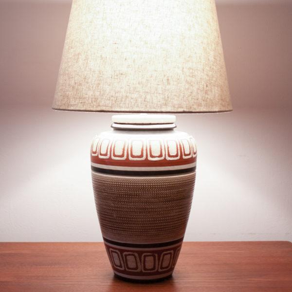 BUENOS DIAS. Das Design der Lampe ist im mexican Style der 50er Jahre. Warme Farben und geometrische Muster kommen hier zusammen. Ein Traumteil! Die erdverbundenen Farben erinnern auch an das INKA-Volk mit Ihren Höhlenmalereien. Die Farbtöne bewegen sich zwischen Sand, Weinrot, Schwarz, und einem erdigen Braun. Das geometrische Muster ist in den getöpferten Korpus eingeritzt.