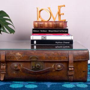 Ein so seltener Lederkoffer aus England macht sich richtig gut als Wohnzimmertisch. Bei der Farbe des Koffers muss eigentlich immer eine Flasche Whiskey und eine Zigarrenschachtel auf dem Tisch liegen, beziehungsweise stehen. Mit soviel Charme braucht es nicht mehr viel für ein gemütliches Arrangement im Wohnzimmer. Natürlich machen sich auch Bücher und Zeitschriften auf dem Koffer richtig gut. Um eine gerade Auflagefläche für Deine Utensilien zu haben, liegt auf dem Koffer eine 5mm dicke Glasplatte. Dadurch dass der Koffer durch sein Alter einen Vintage Zustand hat und nicht mehr ganz gerade ist, ist es möglich etwas zwischen Kofferoberseite und Glasplatte eine Zeitschrift, ein gemaltes Bild, oder wie auf dem Foto eine Vinylplatte gelegt werden kann. Sei kreativ und finde einen schönen Gegenstand, der dort Platz finden kann. Vielleicht auch Deine letzte Konzertkarte. In Zeiten von Corona ja wirklich schon etwas Besonderes. Dieser Koffer ist ein Unikat.